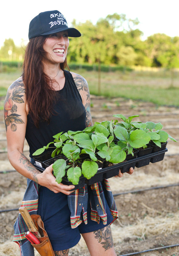 Katina Connaughton carrying potted vegetables on the farm