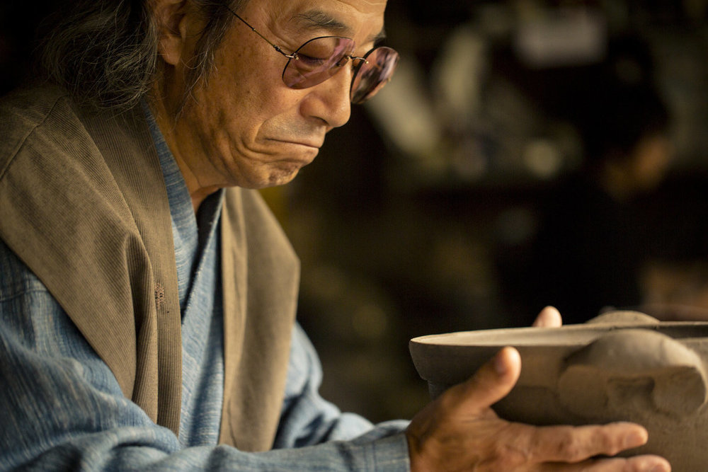 "Mr. Yuji ""Kaicho"" Nagatani in his studio viewing hand made donabe prior to firing"