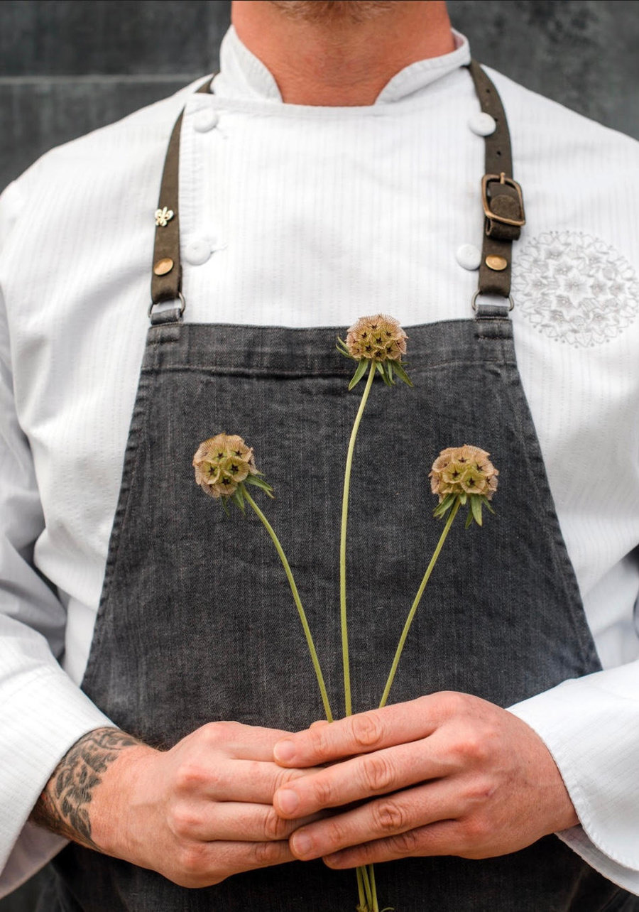 Chef Kyle's hands holding three onion flowers