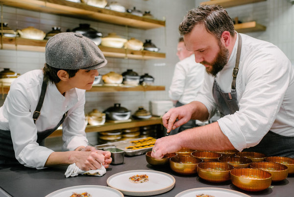 Chef Crenn speaking with member of kitchen team during plating
