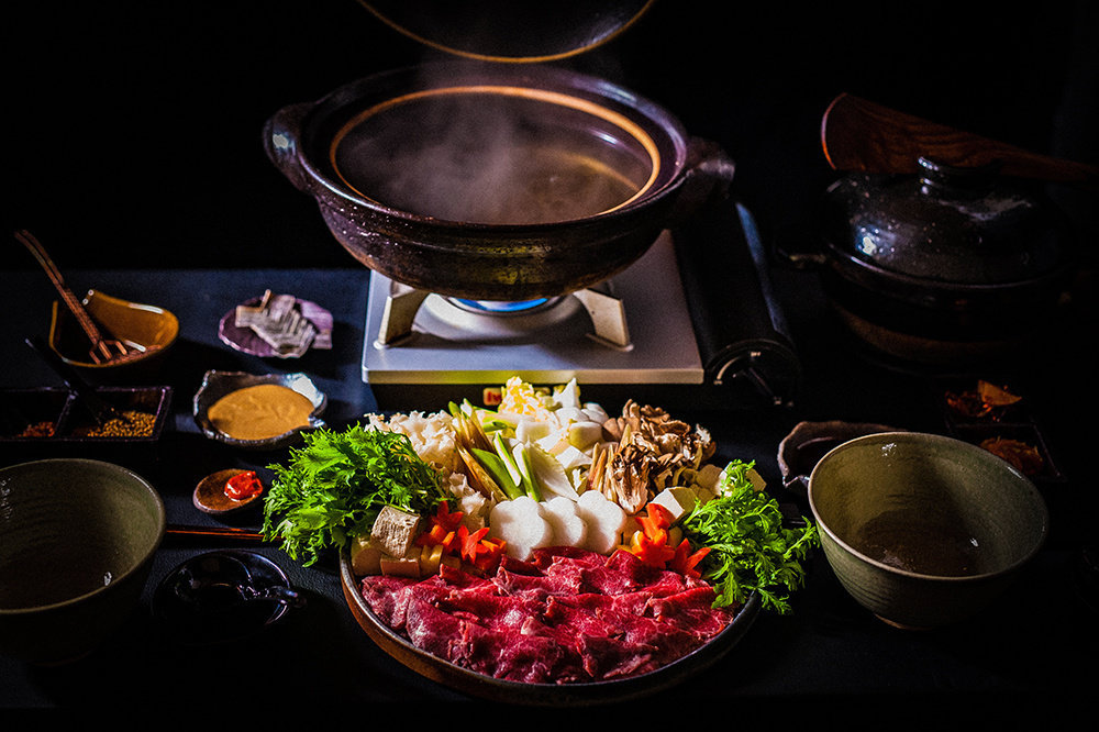 A steaming hot pot of broth surrounded by thinly sliced beef and farm vegetables. Empty bowls for serving, small dishes of sauce and other sides surround the large hot pot.