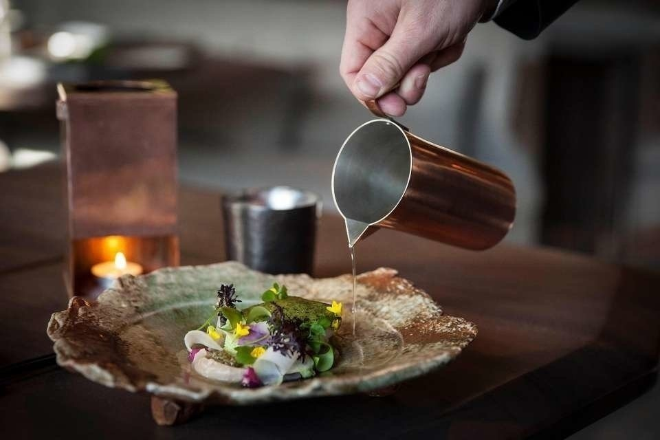 pouring broth onto a dish from a copper vessel