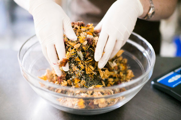 Two hands mixing dried flowers