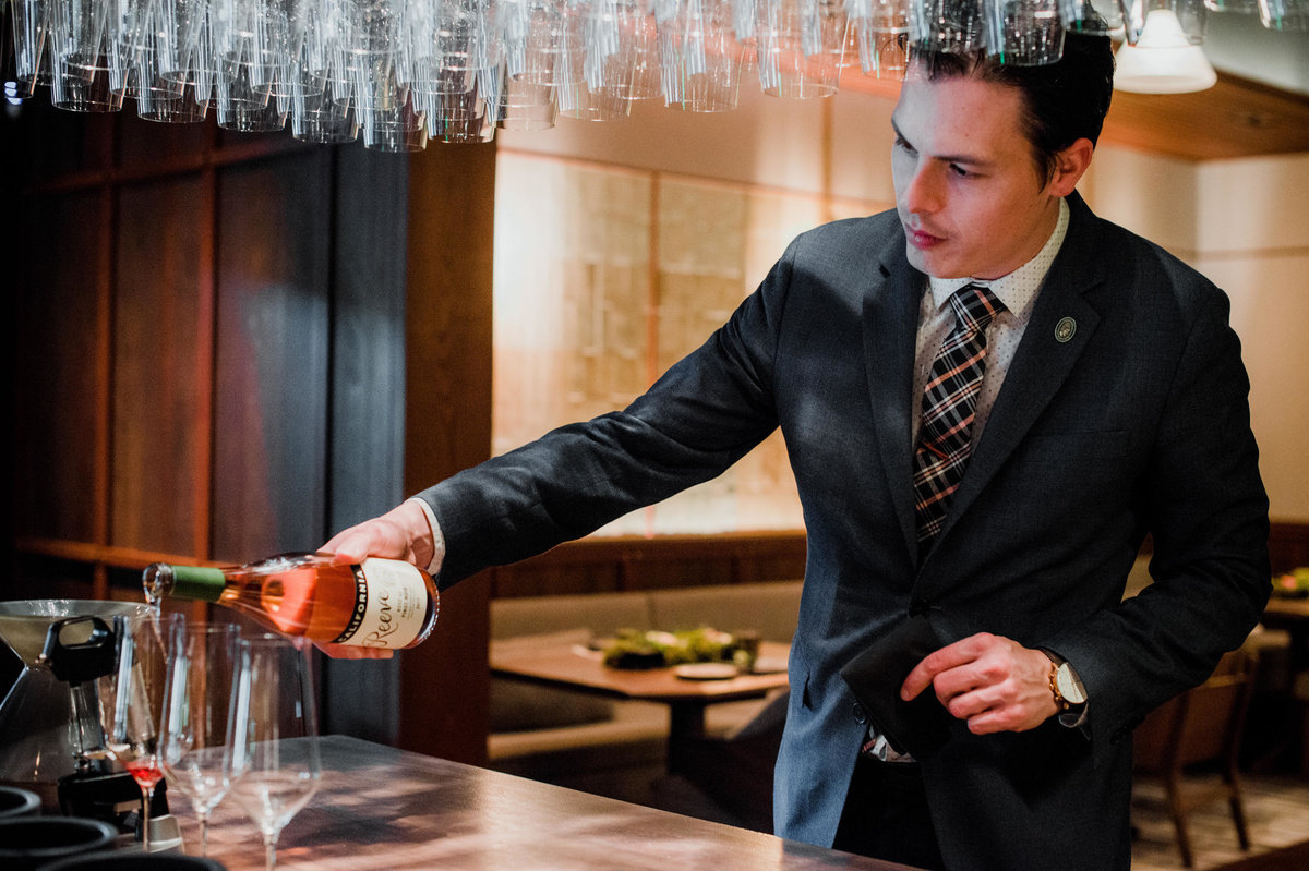 Evan Hufford, Wine Director, pouring wine
