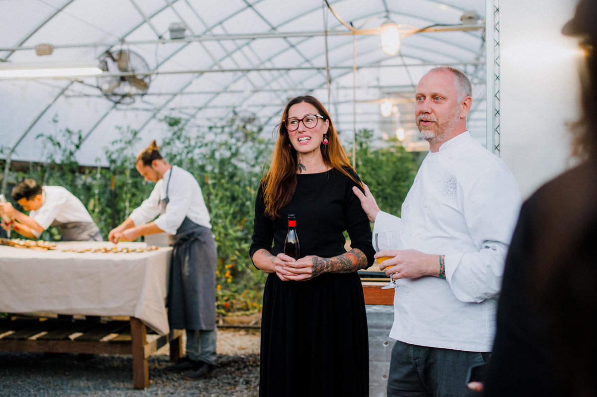 Chef Kyle speaking to guests outside the farm with his hand on wife Katina's shoulder